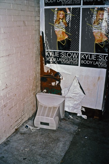 image from Left Behind series: discarded computer monitor against a wall with a poster for Kylie Minogue